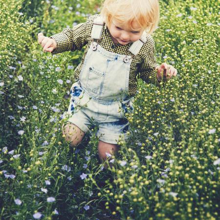 Boy playing in a field of flowers Zdjęcie Seryjne