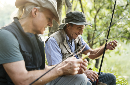 Senior friends fishing by the lake Stock Photo
