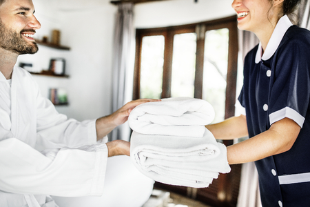 Housekeeper handing over fresh towels 스톡 콘텐츠