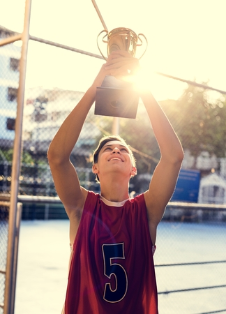 Caucasian teenage boy in sporty clothes holding up a trophy outdoors Reklamní fotografie