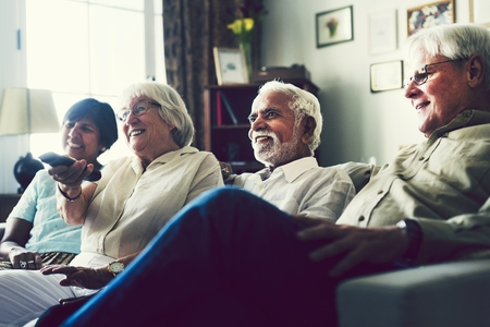 Senior people watching television in the living room Stock Photo