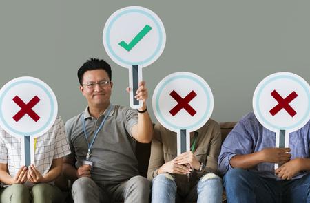 Groupe de personnes tenant des icônes vraies et fausses Banque d'images