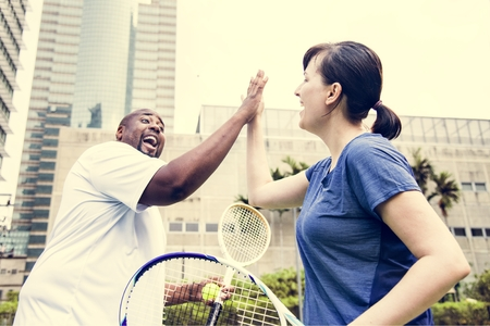Couple playing tennis as a team