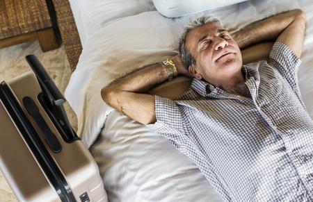 Senior man sleeping on a white bed 写真素材
