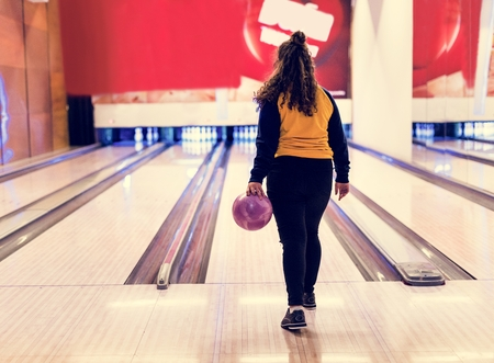 Girl about to roll a bowling ball hobby and leisure concept