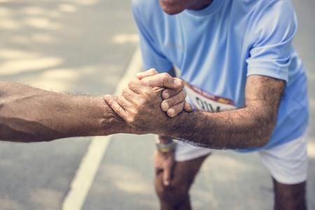 Senior loper die een helpende hand geeft