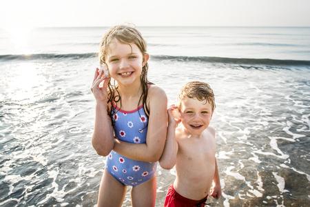 Frères et sœurs s'amusant sur la plage