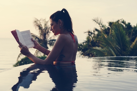 Woman reading a book in the swimming pool Stockfoto