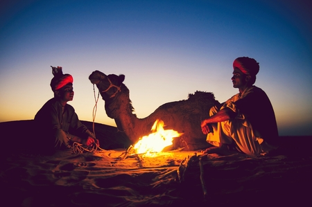 Indian men resting by the bonfire with their camel Stock Photo