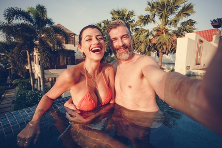 Couple taking a selfie in a pool Banco de Imagens - 110111633