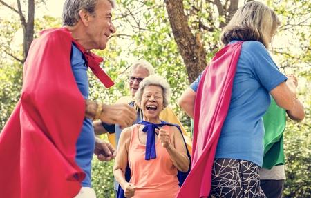 Childlike seniors wearing superhero costumes Imagens