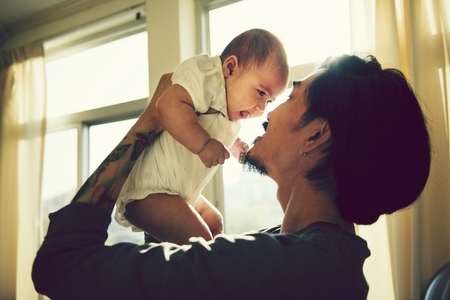 Tattooed father caring for his baby daughter Archivio Fotografico - 110373152