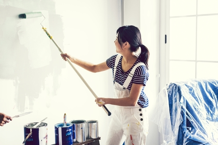 Asian woman painting the wall Stockfoto