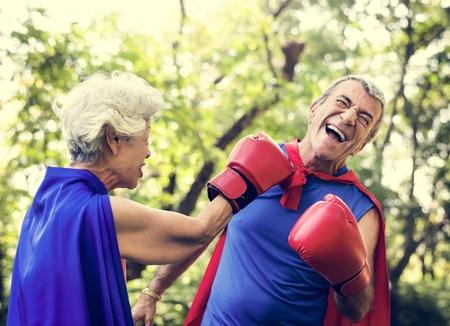Childlike seniors wearing superhero costumes Stock Photo