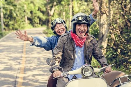 Senior couple riding a scooter classique
