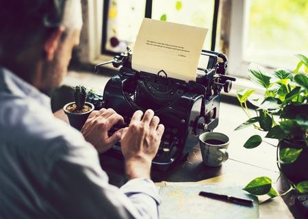 Man typing on a vintage typewriter Фото со стока