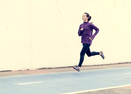 White woman running on track Imagens
