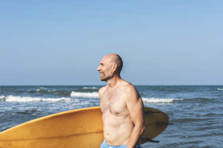 A man with a surfboard by the coast Imagens