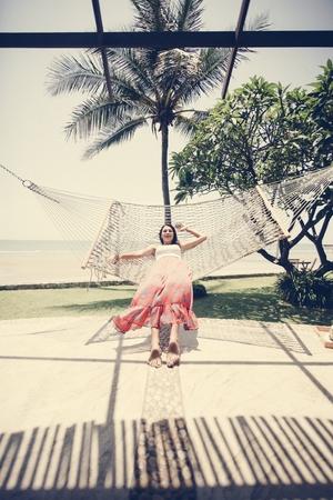Woman sitting in a hammock by the beach