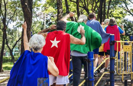Happy seniors wearing superhero costumes at a playground Imagens