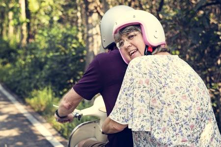 Senior couple riding a classic scooter Imagens