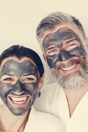 Happy couple wearing a charcoal mask Imagens