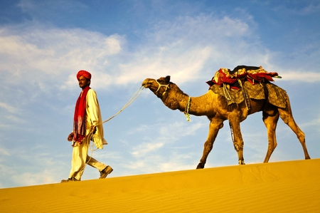 Indian man walking through the desert with his camel 免版税图像