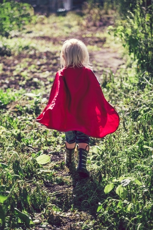 Little superhero walking in a field