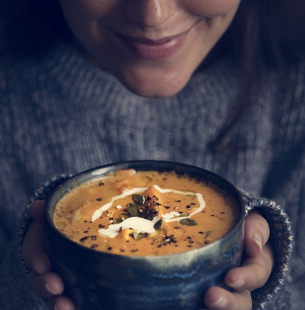 Woman holding a bowl of soup food photography recipe idea 스톡 콘텐츠