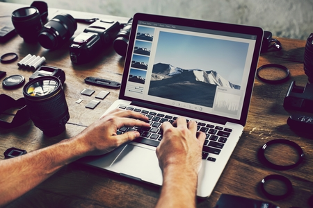 Photographer editing photos on a laptop