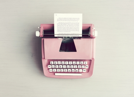 Retro pastel typewriter on grey surface 写真素材