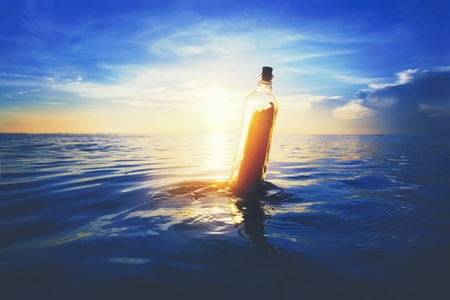 Message in a bottle floating at sea Фото со стока