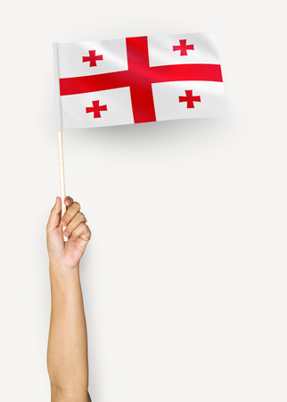 Person waving the flag of Georgia