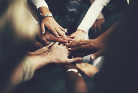 Menschen, die sich als Team zusammenschließen Standard-Bild