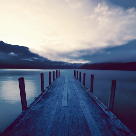 Boat jetty and a calm lake at sunrise, New Zealand