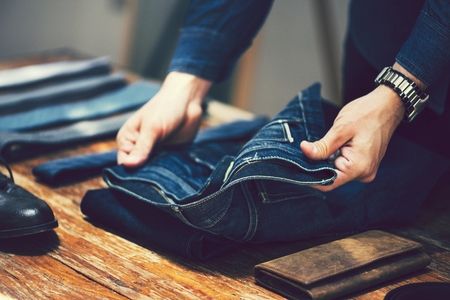 Man unfolding a pair of jeans