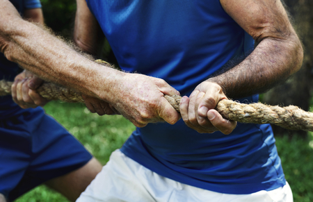 Mature people in tug of war Standard-Bild