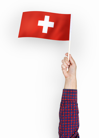 Person waving the flag of Switzerland Stock Photo - 110450794