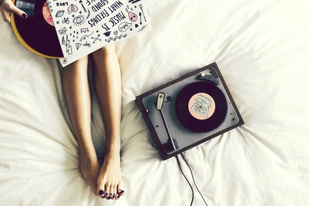Woman listening to music from a vinyl disk turntable