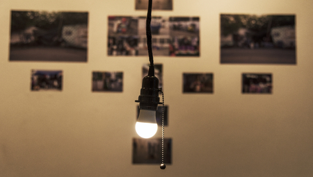 A bright light bulb hanging in a room Foto de archivo - 110451290