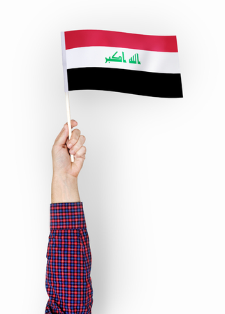 Person waving the flag of Republic of Iraq