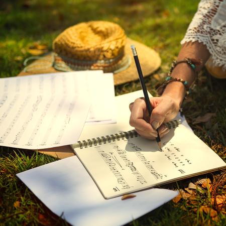 Woman writing a lyric in a notebook 免版税图像 - 110451767