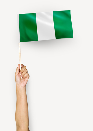 Person waving the flag of Federal Republic of Nigeria Stock Photo