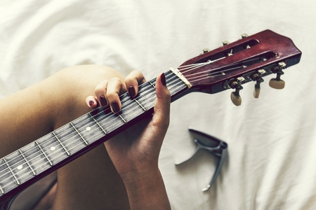 Woman playing guitar on her bed