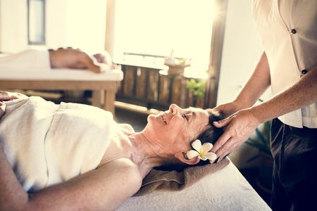 Female message therapist giving a massage at a spa Stock Photo