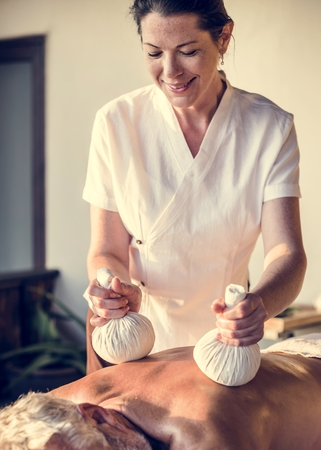 Female message therapist giving a massage at a spa Imagens