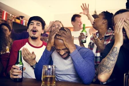 Amici che incoraggiano insieme lo sport al bar