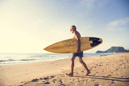 Mature surfer ready to catch a wave Фото со стока