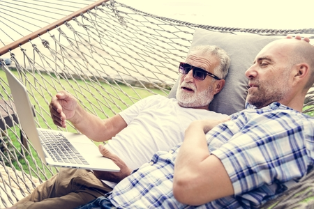 Senior men lying on a hammock using a laptop