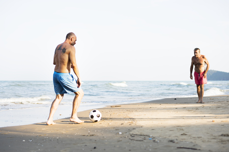 Men playing football at the beach